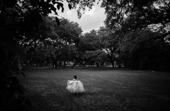 A little girl walks into a field at The Verandah San Antonio Leica Wedding Photographer - A 100 Weddings Later by Philip Thomas