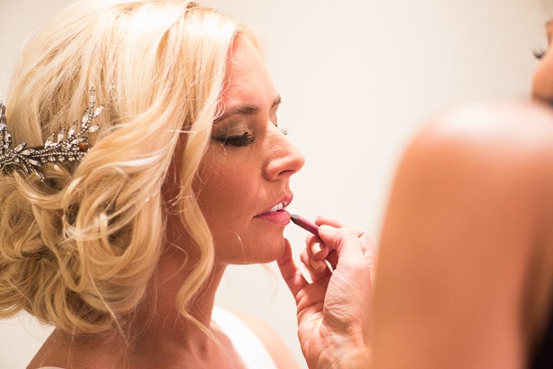 Bride applying makeup