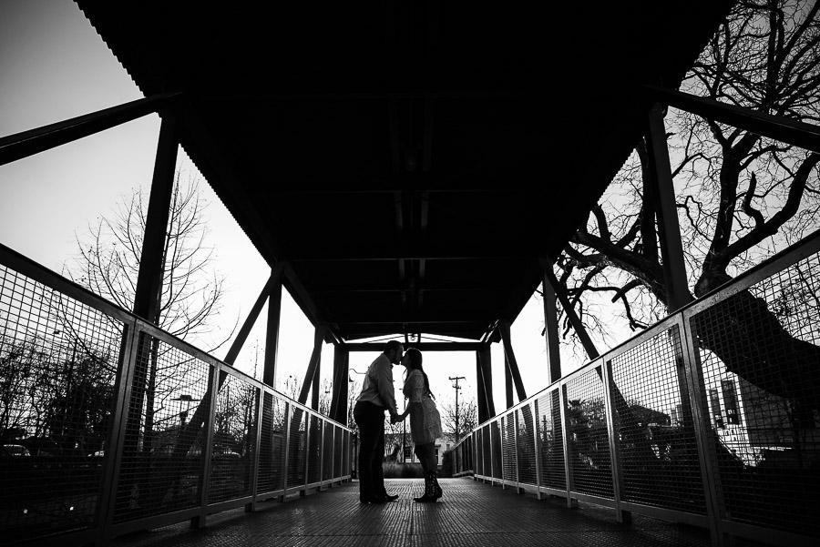 Couple engaged on bridge silohetted