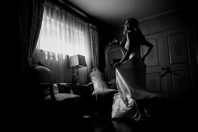 Bride picks up her dress and turns near window Madera Estates-Philip Thomas