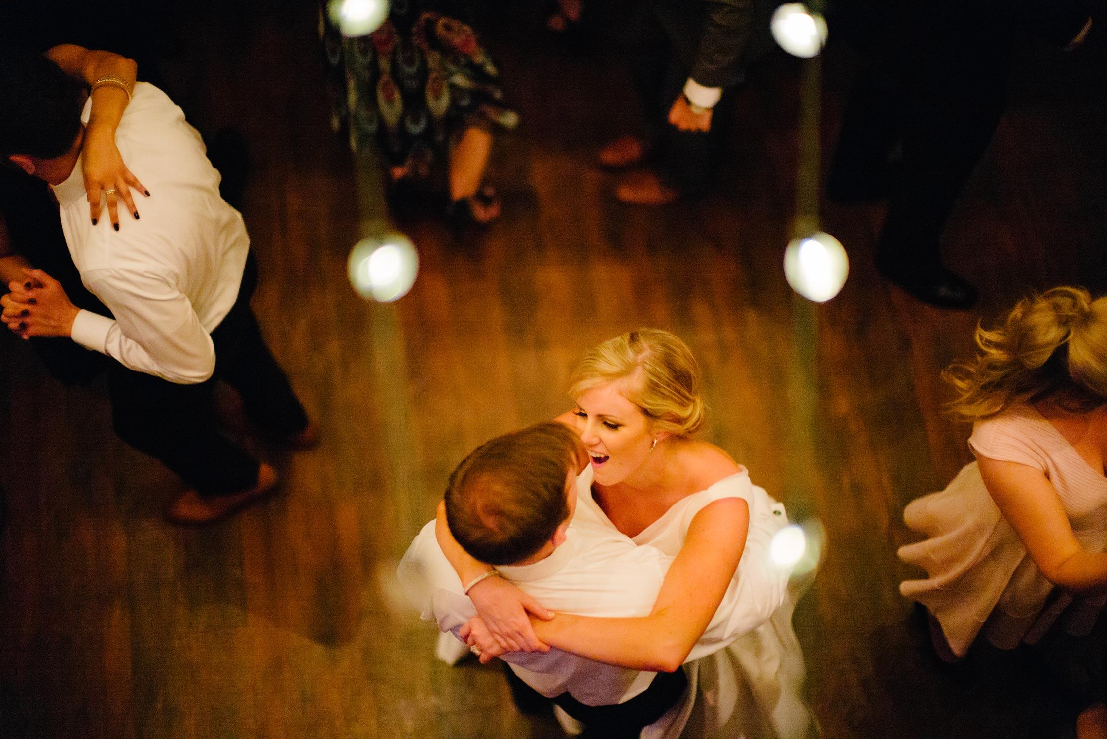 Couple first dance under edison style lightbulbs wedding reception best-houston-wedding-photographers