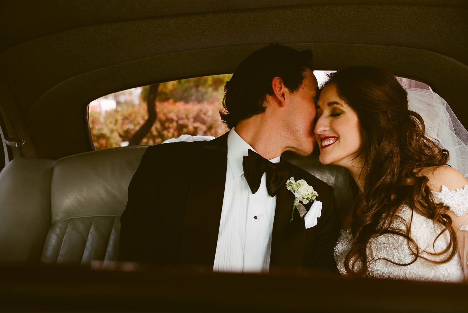 Bride and groom share a moment kiss check to cheek in back of antique car on wedding day la-cantera-resort-wedding-photographer-philip-thomas