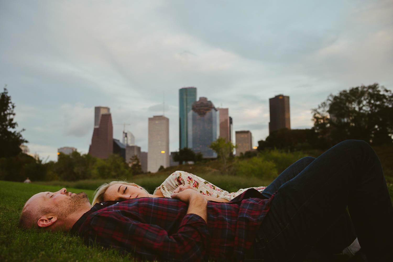 downtown-houston-skyline-engagementshows couple lying in the grass-leica-wedding-photographer-philip-thomas