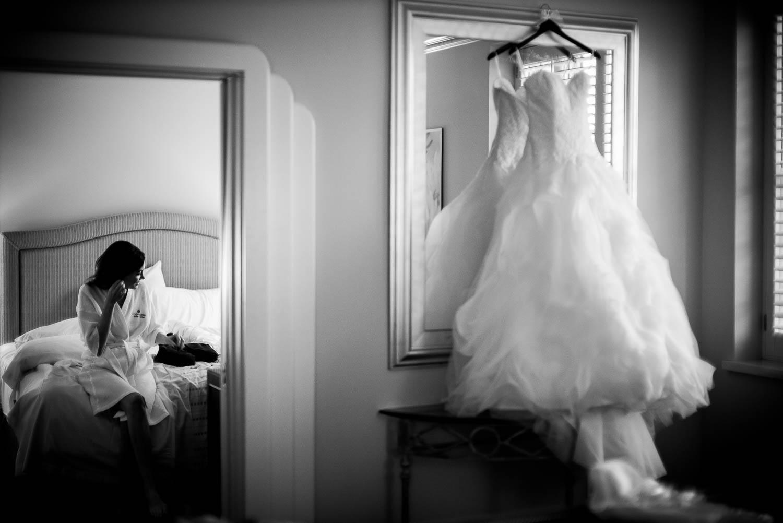Bride wears earrings sitting in hotel room at Hotel Galvez Galveston Wedding in Texas