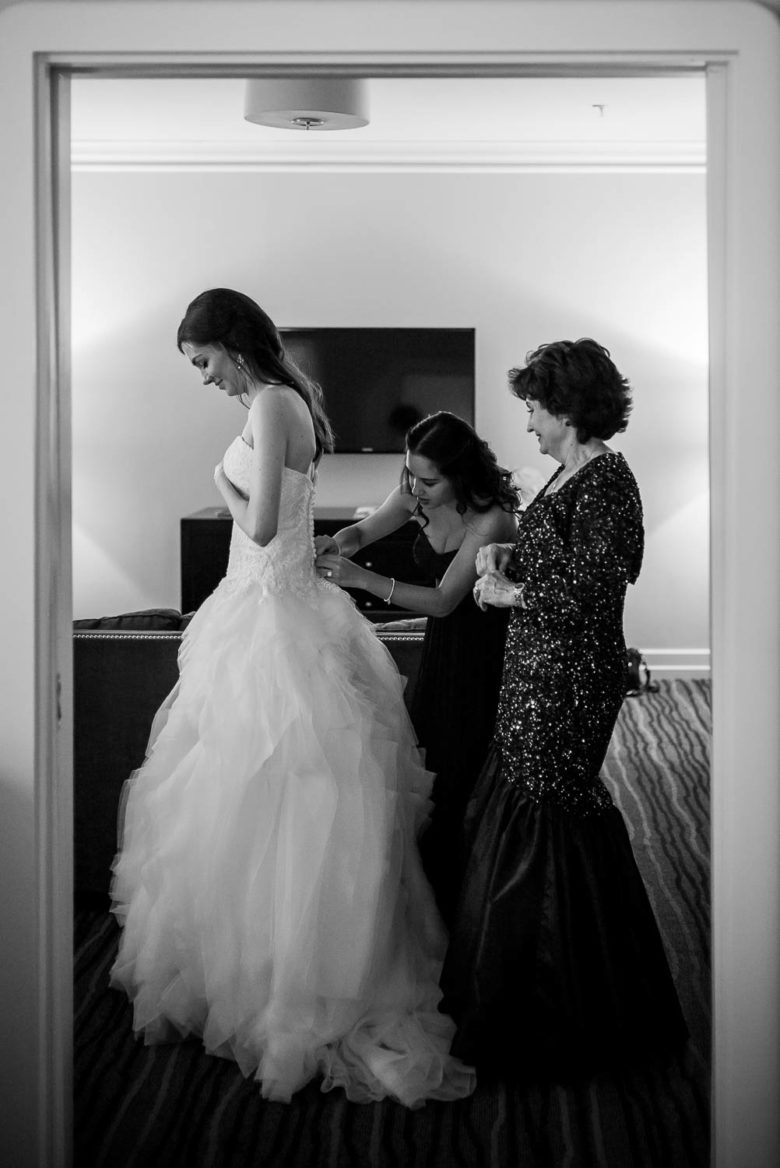 Bride, Maid of honor and mother help bride get ready photographed in a door frame at Hotel Galvez Galveston Wedding in Texas