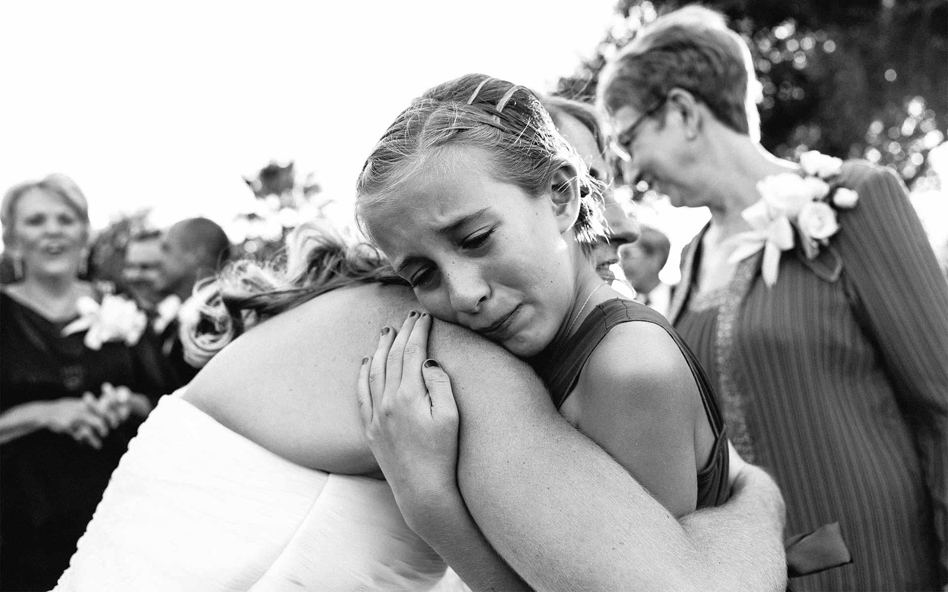 Upset flower girl hugs bride Leica wedding photographer