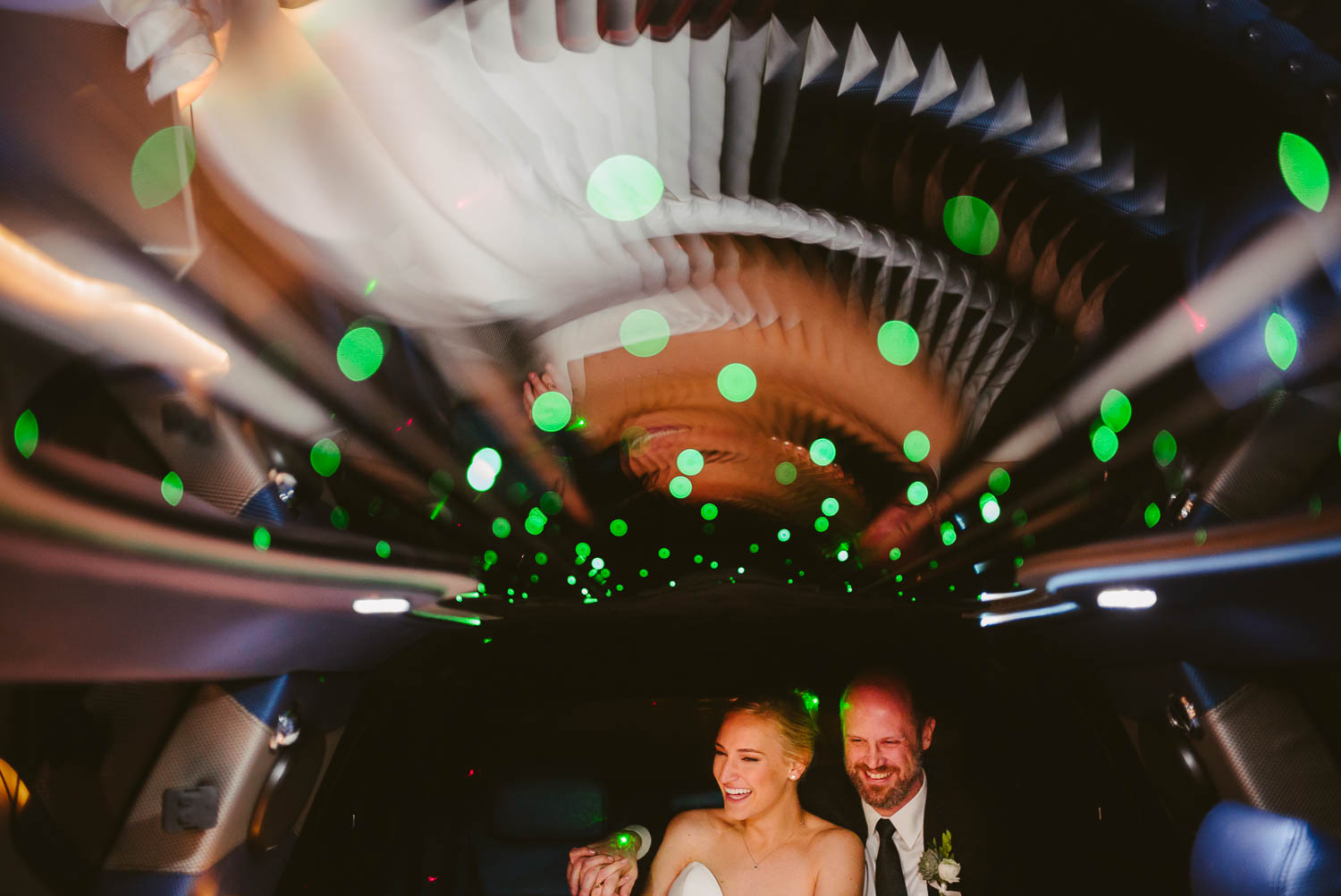 Couple share a funny moment inside a limo with green sparkling lights Houston Texas en route to Brennan's of Houston, Texas.