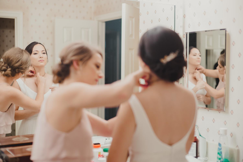 Bride checks the mirror after getting dressed at Cherie Flores Garden Pavilion Wedding Hermann Park Houston Texas-Philip Thomas