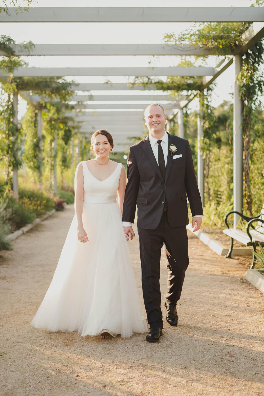 Couple walk through trellis at sunset on their wedding day Cherie Flores Garden Pavilion Wedding Hermann Park Houston Texas-Philip Thomas