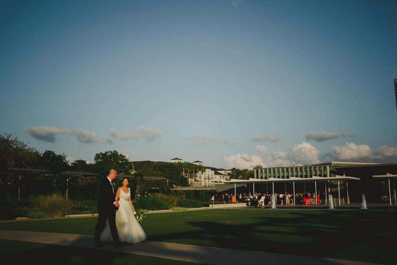 Just married couple stride across park at Cherie Flores Garden Pavilion Wedding Hermann Park Houston Texas-Philip Thomas