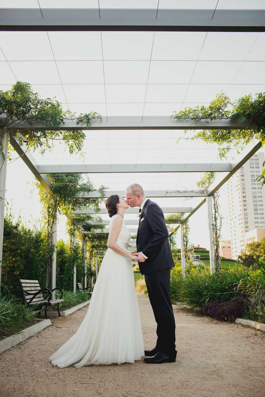 Couple kiss at Cherie Flores Garden Pavilion Wedding Hermann Park Houston Texas-Philip Thomas
