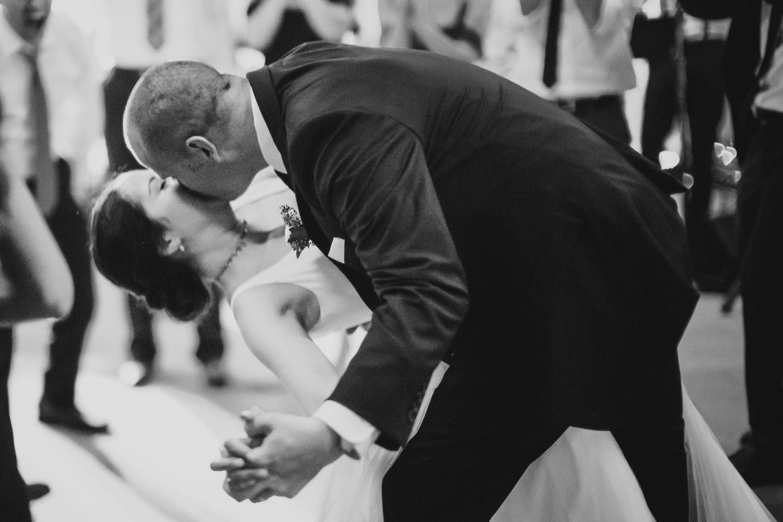 Groom lowers bride for a kiss on dance floor reception Cherie Flores Garden Pavilion Wedding Hermann Park Houston Texas-Philip Thomas