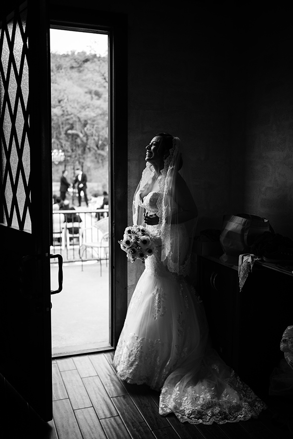 Lilly, the bride reacts to peeping around the door frame and see her future husband, Frank moments before the wedding ceremony starts. Photographed in Texas with a Leica M10-P and a 35mm summilux lens, photographed by Philip Thomas