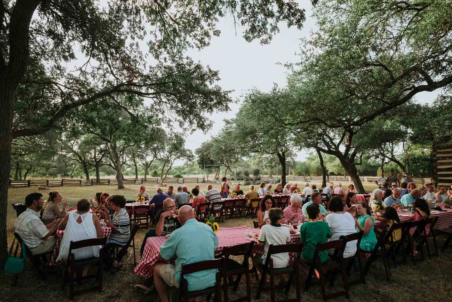 Friends and family gather round long table setups at a wedding rehearsal dinner