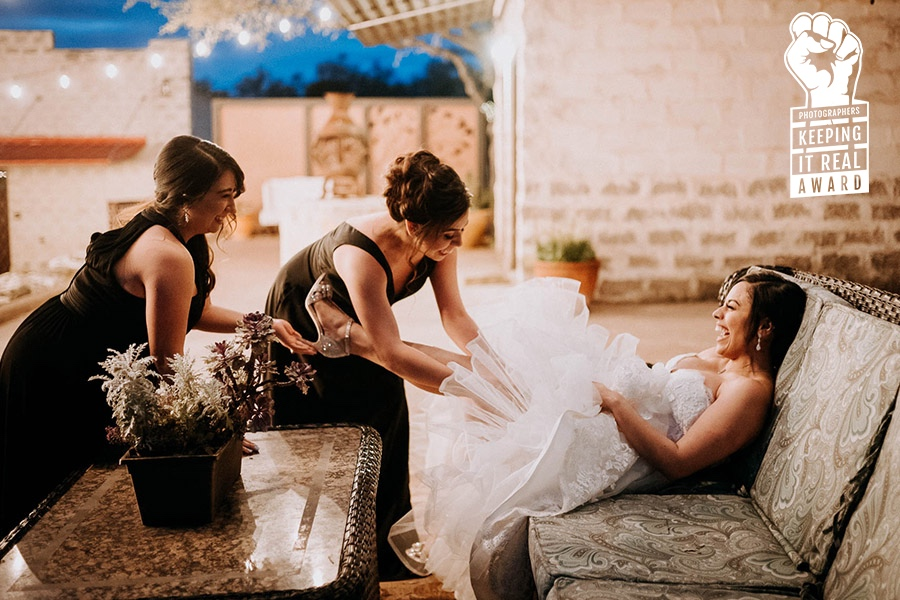Photographers Keeping It Real - Award winning iage by Philip Thomas shows the mother and sister of bride adjusting her garter
