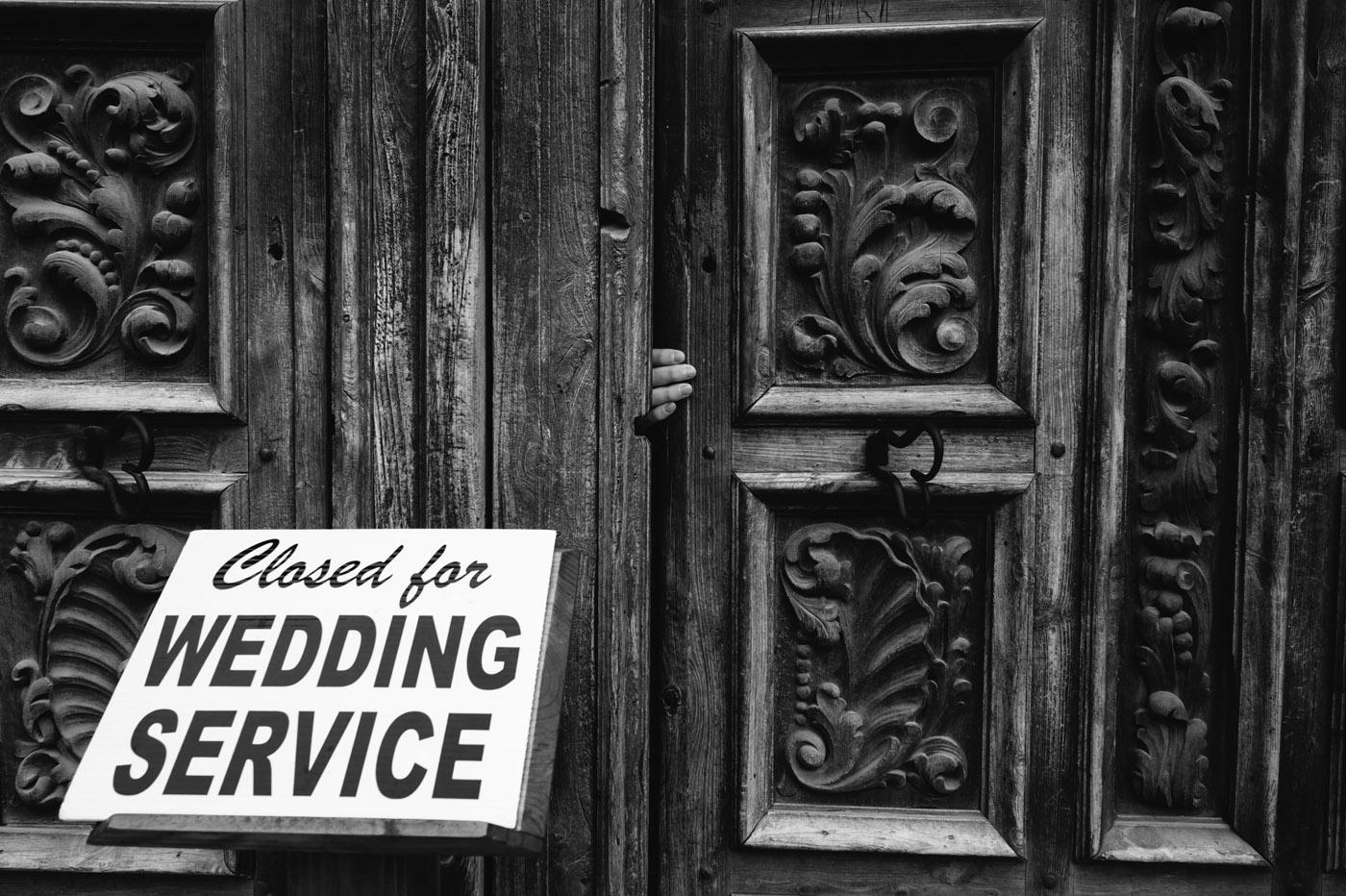 A hand opens the San Jose Missions door San Antonio Wedding Photographer